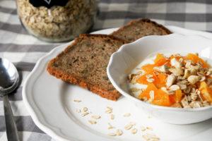 Frühstück mit Joghurt, Nüssen, Haferflocken und Orangen